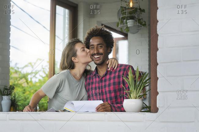 Woman kissing her boyfriend on cheek in cafe