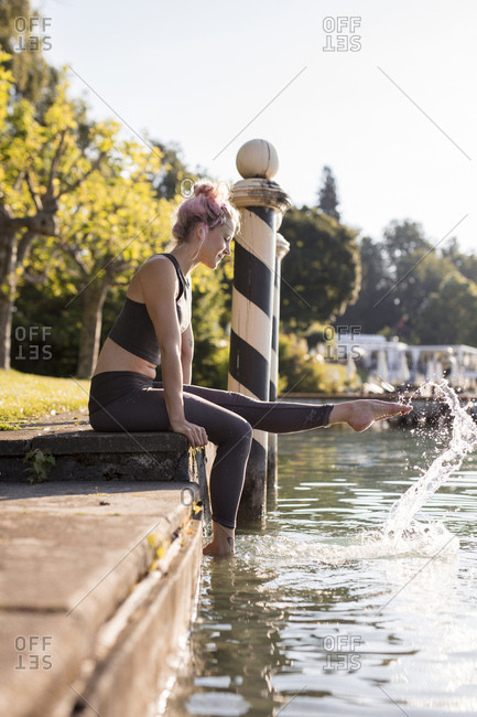 Woman in sportswear sitting at lakeshore with feet in water