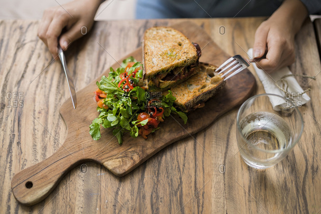 Hands holding knife and fork at wooden table with decorated salad and crusty bread