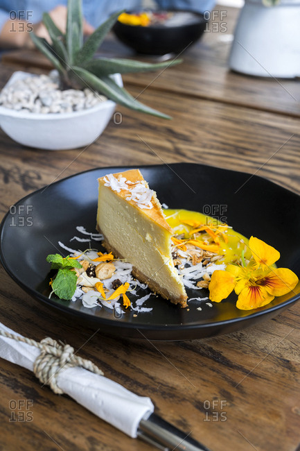 Decorated cheesecake piece with flowers on wooden table