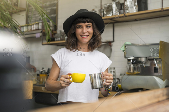 Portrait of woman with black hat behind the bar preparing a coffee