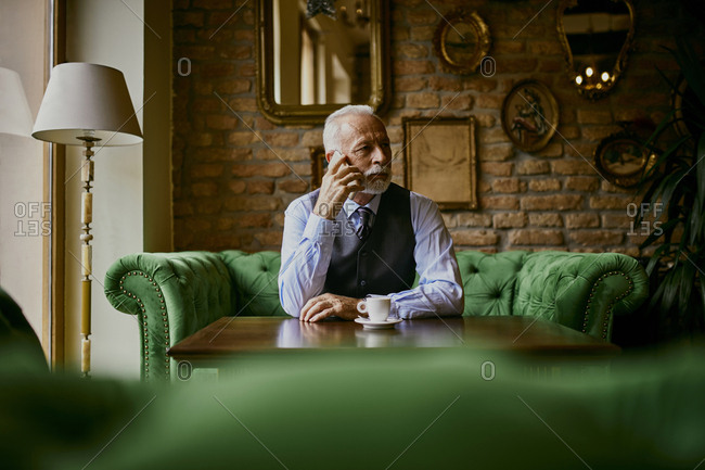Elegant senior man sitting on couch in a cafe on cell phone