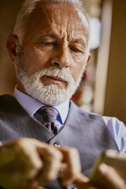Elegant senior man using cell phone
