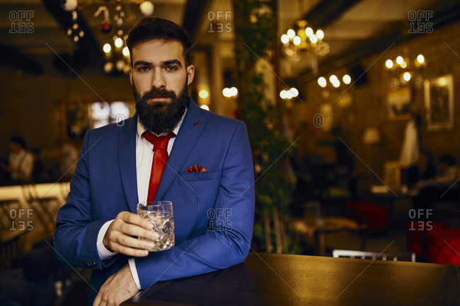 Portrait of elegant young man in a bar holding tumbler