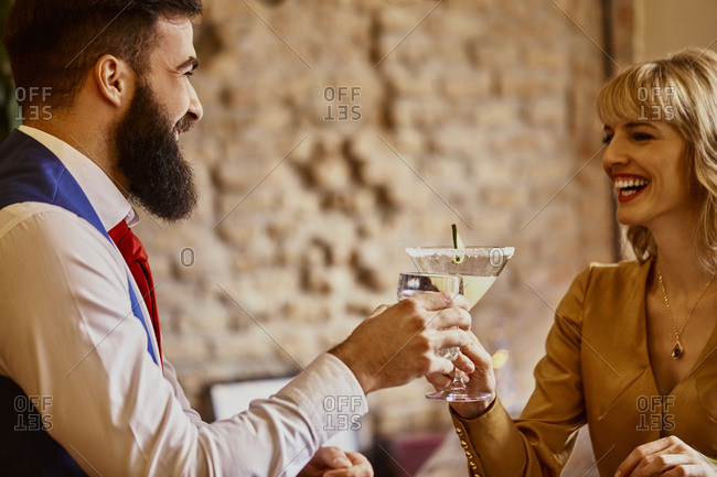 Happy elegant couple toasting glasses in a bar