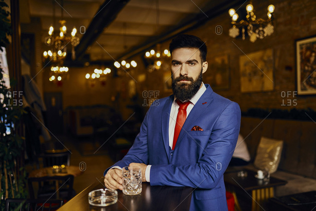 Portrait of elegant young man in a bar with tumbler