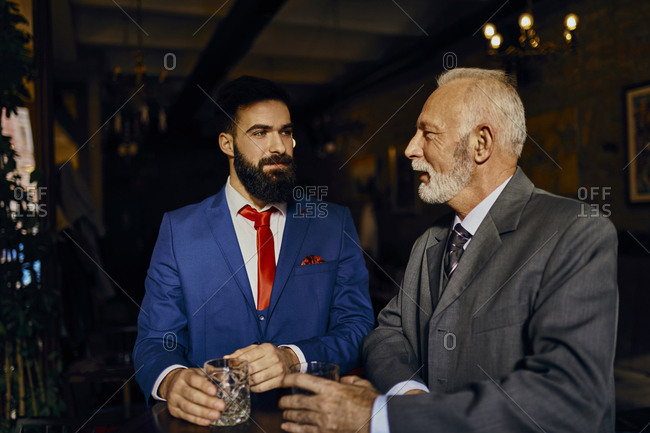 Two elegant men in a bar with tumblers