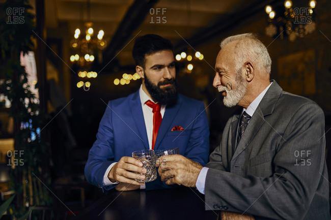 Two elegant men in a bar clinking tumblers