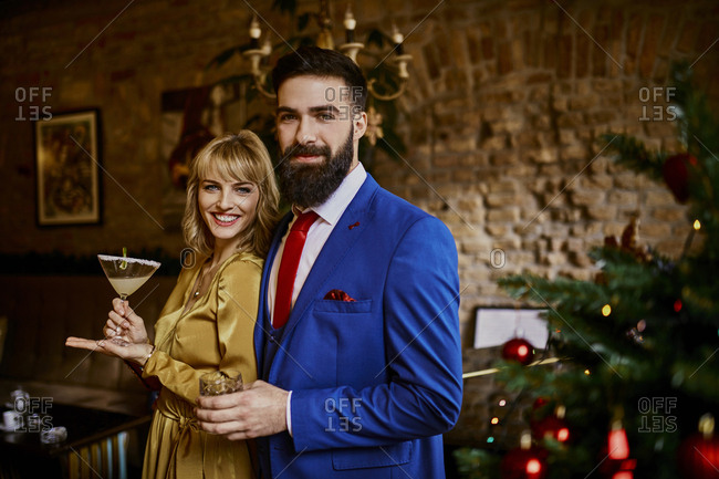 Portrait of elegant couple with drinks at Christmas tree