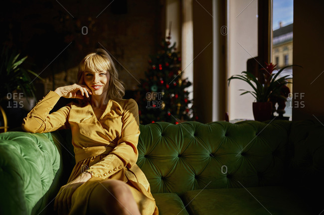 Portrait of smiling elegant woman sitting on a couch with Christmas tree in background