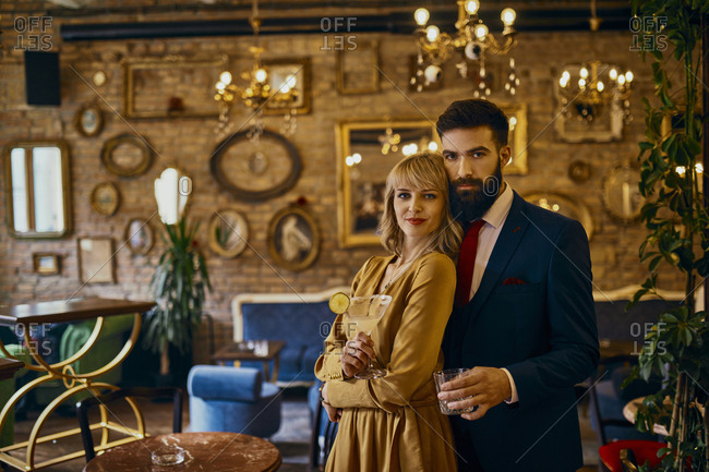 Portrait of elegant couple with drinks in a bar