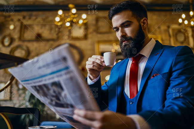 Elegant man drinking coffee and reading newspaper in a cafe