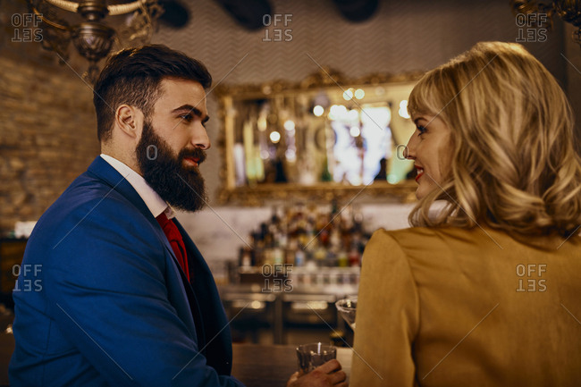 Elegant couple smiling at each other in a bar