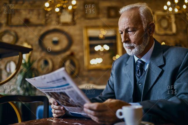 Elegant senior man reading newspaper in a cafe