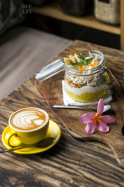 Exotic muesli with flower and coffee cup on a wooden table