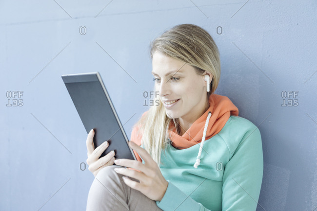 Portrait of smiling woman with tablet listening music with wireless earphones