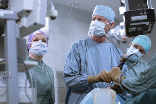 Team of neurosurgeons in scrubs during an operation
