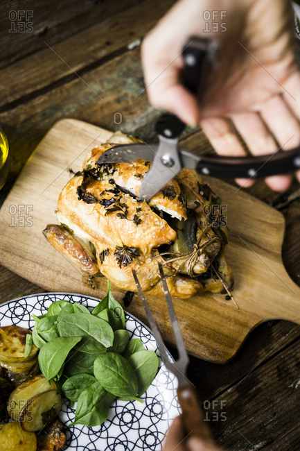 Woman jointing freshly cooked chicken