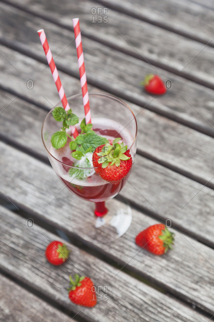 Strawberry lemonade in glass with drinking straws