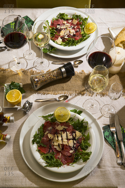 Beef carpaccio on rocket on festive laid table