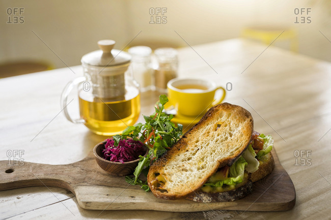 Crusty bread with green salad and beetroot on wooden plate and green tea in cafe