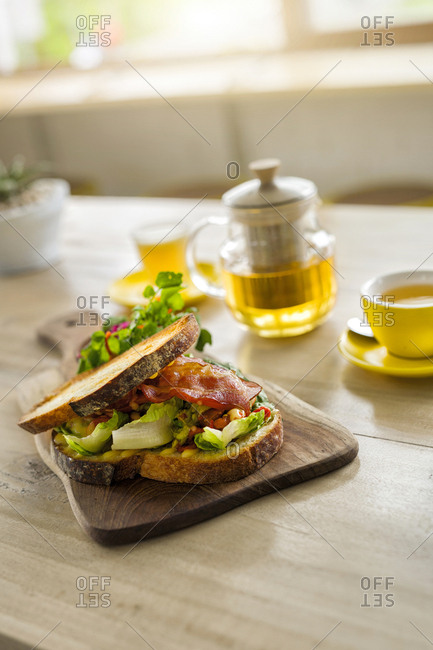 Crusty bread with green salad and ham on wooden plate and green tea in cafe
