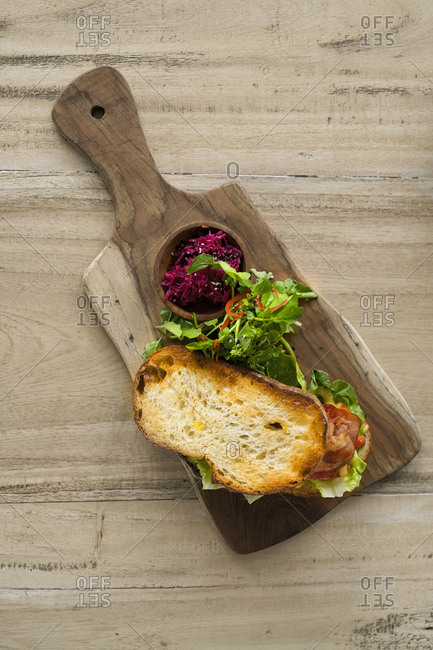 Crusty bread with green salad and ham on wooden plate