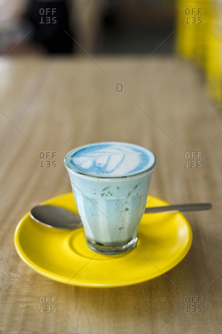 Blue smoothie latte with spirulina in glass on yellow saucer