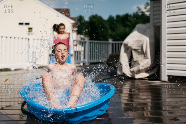 Young boy landing in plastic pool on deck with friends
