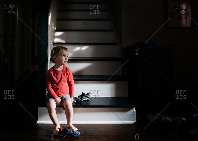 Serious little boy sitting alone at bottom of stairs
