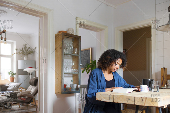 Woman reading book in kitchen