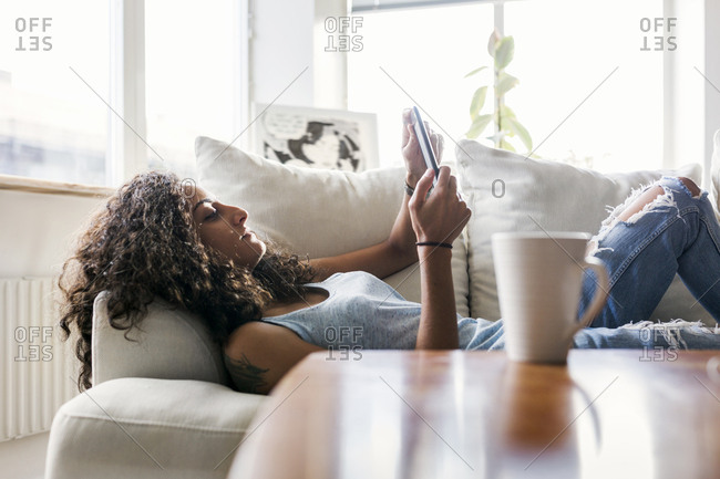 Woman lying down on sofa and using e-reader