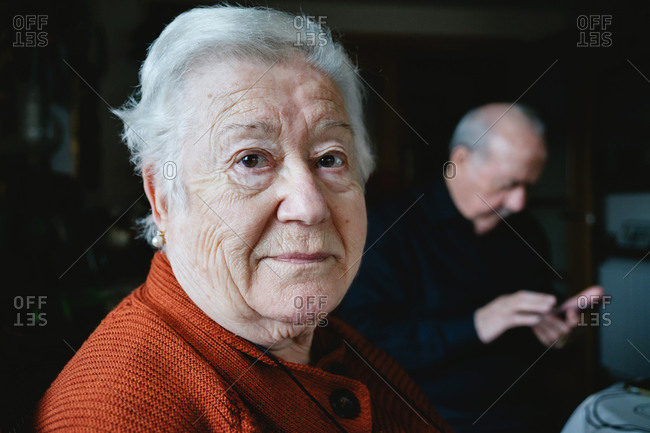 Portrait of grandmother at home with grandfather in background