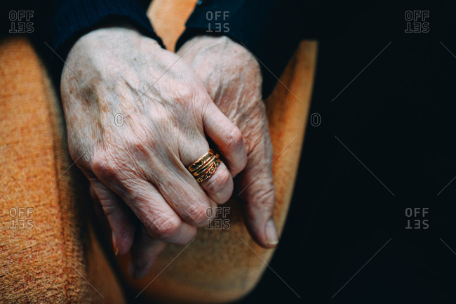 Close-up of elderly couple's hands clasped together at home