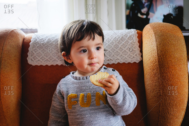 Toddler eating a cookie in living room chair