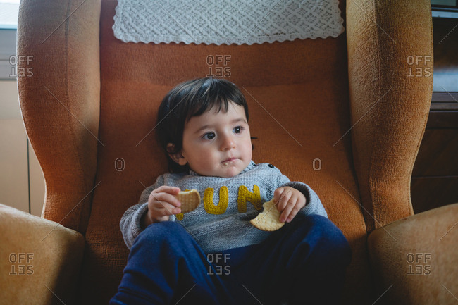 Young girl eating multiple cookies in a big chair