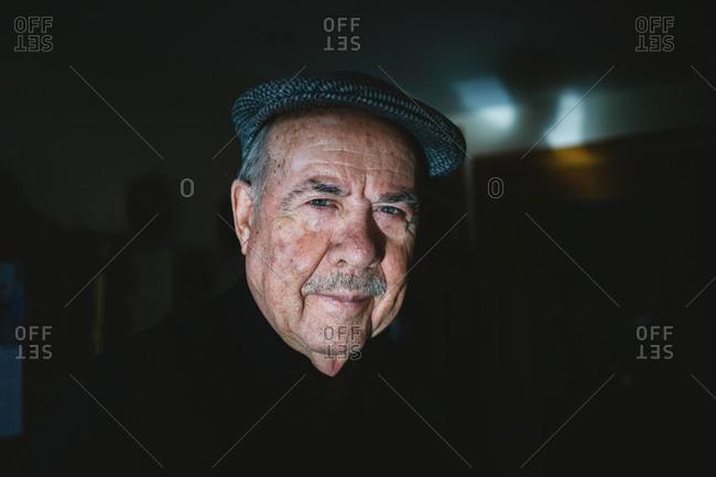 Elderly man wearing hat in dark room
