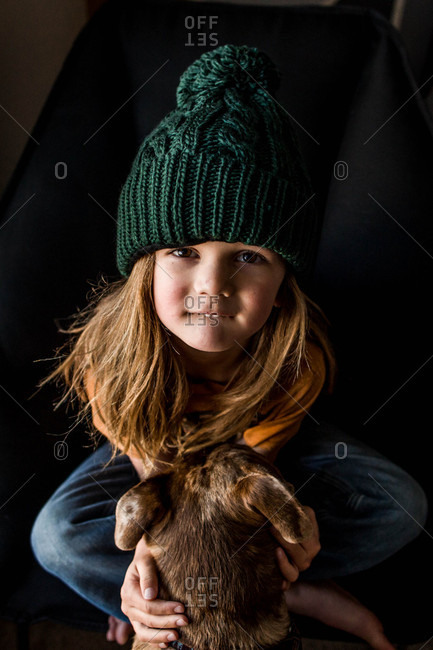 Portrait of a boy with long hair wearing a knit hat and holding a rabbit