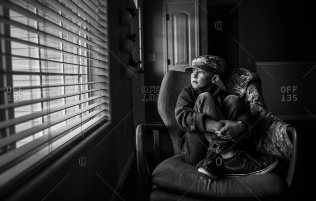 Boy sitting in chair looking out window