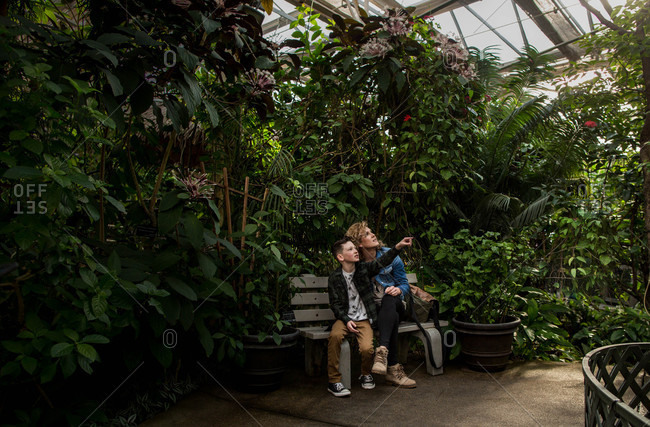Woman and child sitting together on bench surrounded by plants in conservatory