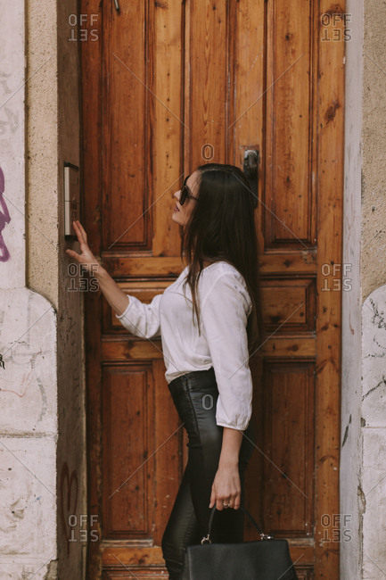 Woman using call button intercom at entrance to building