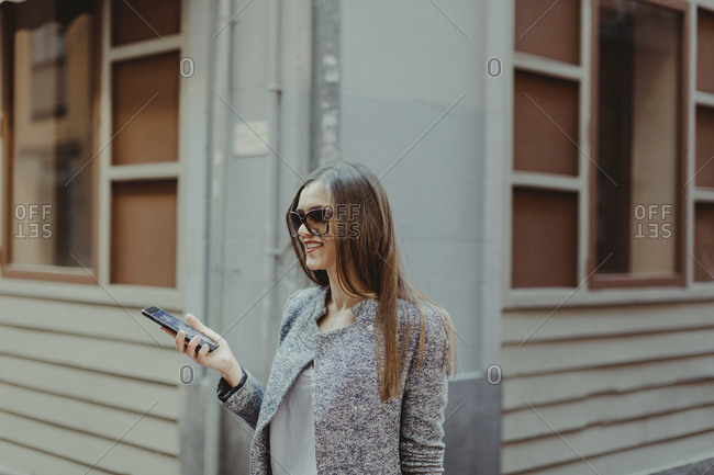 Portrait of a woman with brown hair holding a smartphone