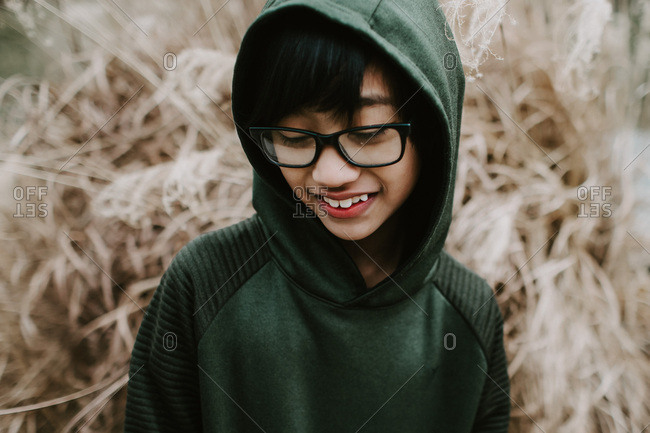 Young boy with glasses shyly looking away