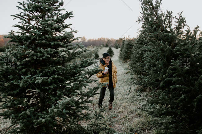 Young boy holding a cup walking among pines at tree farm