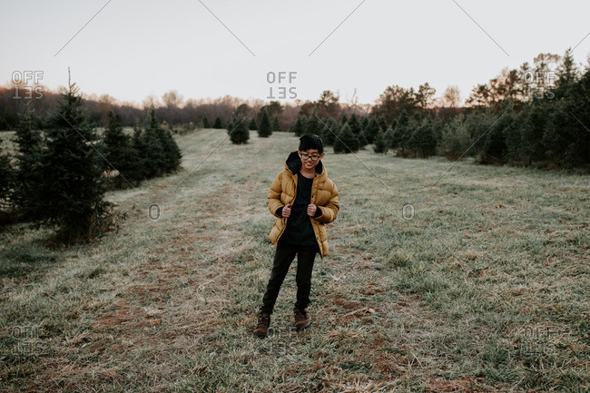 Bashful young boy standing in a field of pine trees