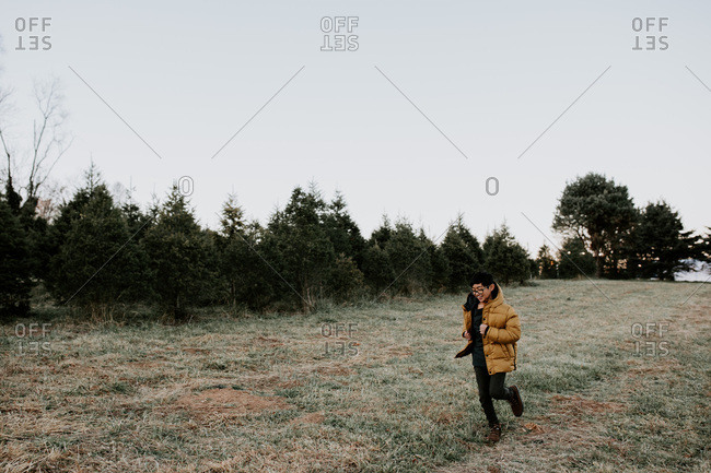Young boy running in a field of pine trees