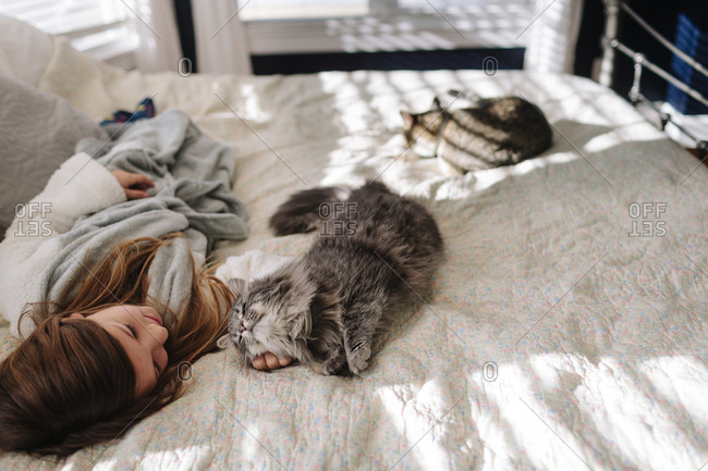 Girl relaxing on bed petting fuzzy cat