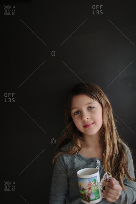 Girl standing against wall holding mug of tea