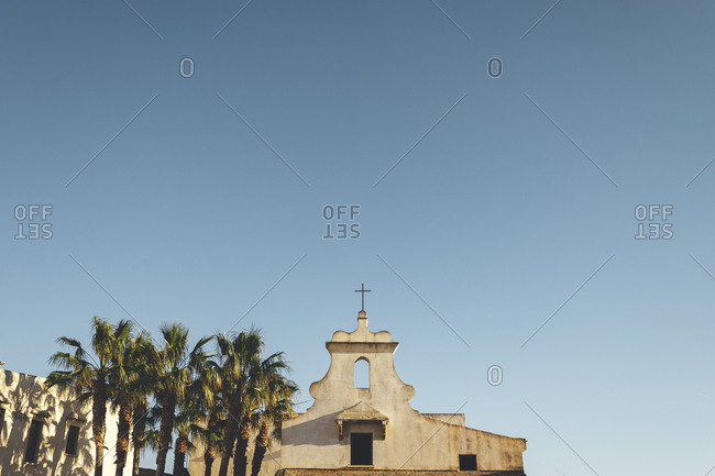 Low angle view of small church and palm trees against big open sky