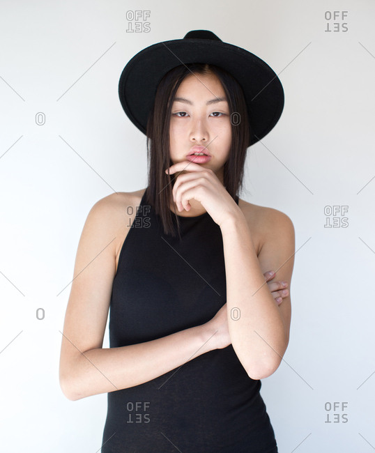 Young Asian woman with posing in studio with hat